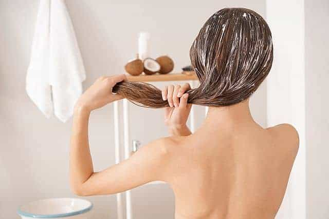Woman applying coconut oil to her hair in the bathroom