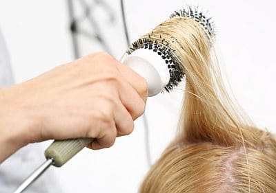 straightening hair with a hot air brush
